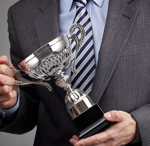 Person in a suit holding a trophy