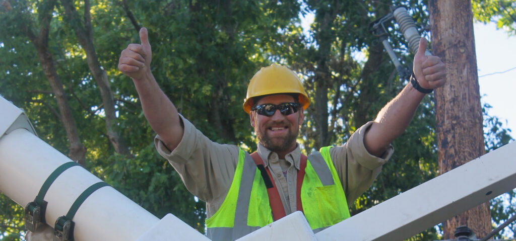Lineworker giving thumbs up in the bucket of  the truck.